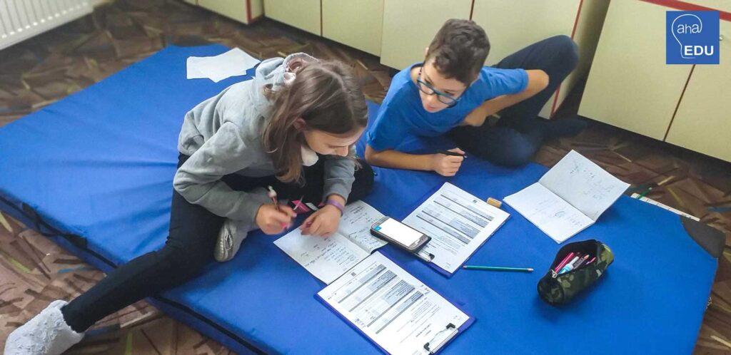 Copiii participa la atelierul Aha Mate lucreaza la un proiect aplicat.